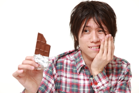 suffers: young Japanese man suffers from toothache