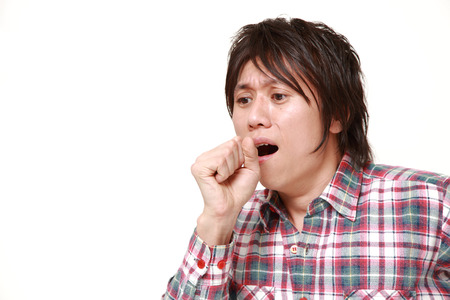 coughing: young Japanese man coughing Stock Photo