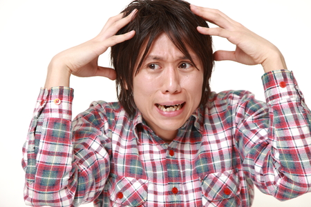 perplexed: young Japanese man perplexed Stock Photo
