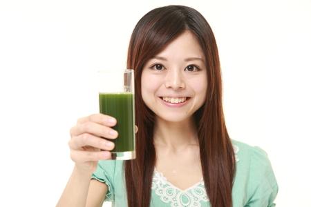 jugo verde: Mujer con el jugo de vegetal verde Foto de archivo