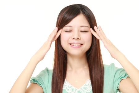 自己の頭のマッサージをしている日本の若い女性 写真素材
