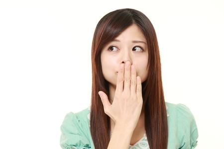 Japanese woman making the speak no evil gesture Imagens