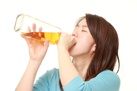 drunkenness: Woman drinking straight from a bottle