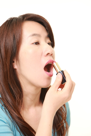 applying lipstick: Japanese woman applying lipstick