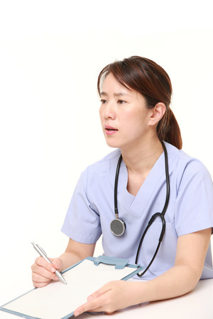 talks: Japanese female doctor with clinical record talks to her patient