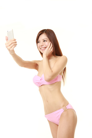 pink bikini: young Japanese woman in a pink bikini takes a selfie Stock Photo