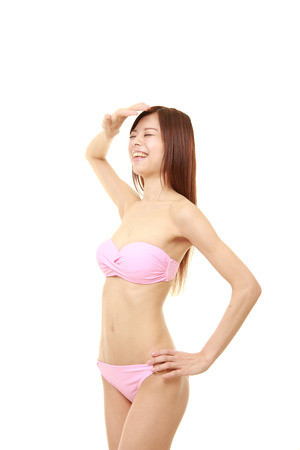 pink bikini: young Japanese woman in a pink bikini looking up shading her eyes
