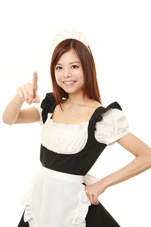 若い日本女性の身に着けているフランスのメイド コスチュームを提示し、何かを示す