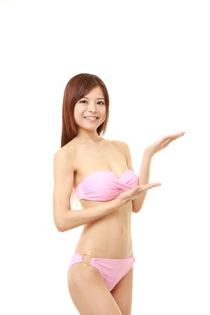 traje de bano: joven japonesa en un bikini rosado presenta y que muestra algo Foto de archivo