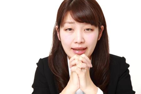remorse: businesswoman folding her hands in prayer