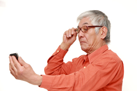 long sightedness: senior Japanese man with presbyopia