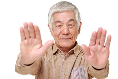 stop gesture: senior Japanese man making stop gesture