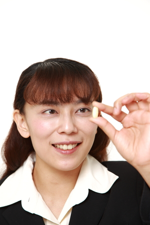 supplement: asian businesswoman takes a supplement Stock Photo