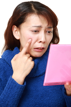 worries: asian woman worries about dry rough skin
