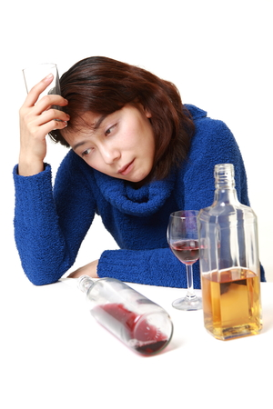 drunkenness: asian woman in depression is drinking alcohol Stock Photo