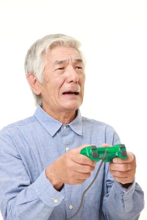losing control: senior Japanese man losing playing video game