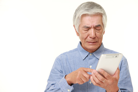 confusion: senior Japanese man using tablet computer looking confused Stock Photo