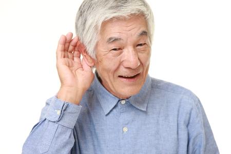 密接に聞く耳の後ろに手で上級日本人男性 写真素材