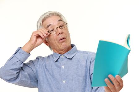 long sightedness: senior Japanese man with presbyopia