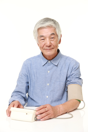 high blood pressure: senior Japanese man checking his blood pressure Stock Photo