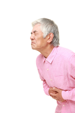 suffers: senior Japanese man suffers from stomachache Stock Photo