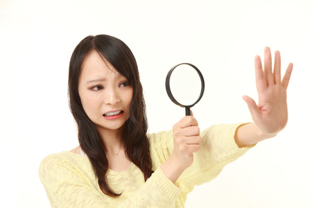 shocked young woman looking through a magnifying glass her nails 写真素材
