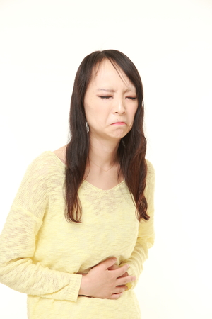 fart: young Japanese woman suffers from stomachache Stockfoto