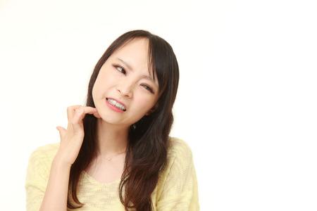 Japanese woman scratching her neck Фото со стока