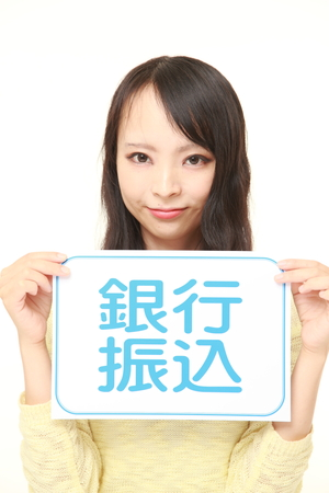 bank overschrijving: businesswoman holding a message board with the phrase BANK TRANSFER in KANJI