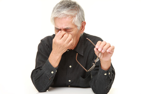 眼精疲労に苦しんでいる年配の日本人男性