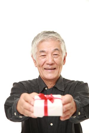 senior Japanese man offering a gift