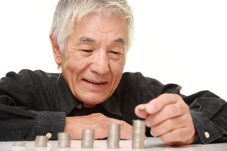 monete antiche: anziano uomo giapponese messo monete pila di monete Archivio Fotografico