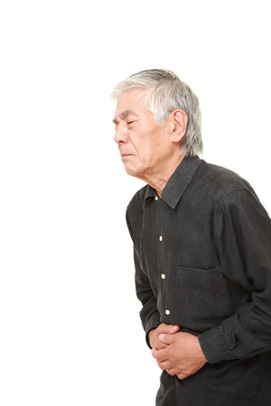 old asian: senior Japanese man suffers from stomachache Stock Photo