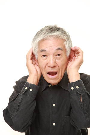 oido: senior Japanese man with hand behind ear listening closely