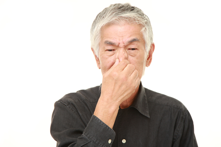 senior Japanese man holding his nose because of a bad smell Stock Photo