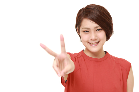 sign: young Japanese woman showing a victory sign