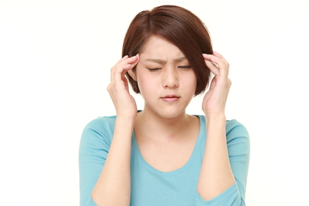 suffers: young Japanese businesswoman suffers from headache