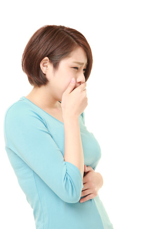 hair problem: young Japanese woman suffers from stomachache Stock Photo