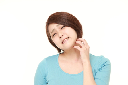 Japanese woman scratching her neck Stock Photo