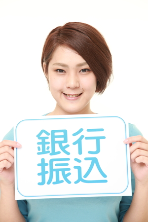 bank overschrijving: woman holding a message board with the phrase BANK TRANSFER in KANJI Stockfoto