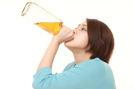 ebrio: joven japonesa que bebe directamente de una botella Foto de archivo