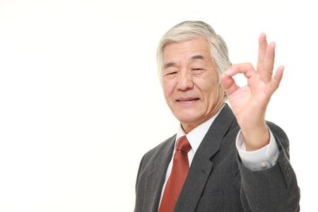 senior Japanese businessman showing perfect sign Stock Photo