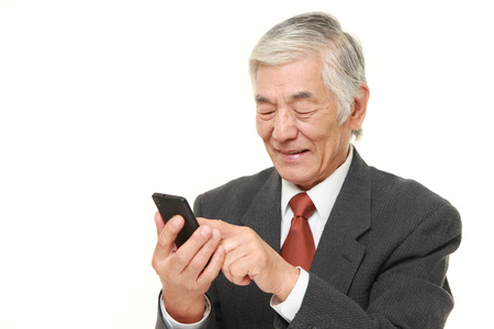 messaging: senior businessman with a smart phone Stock Photo