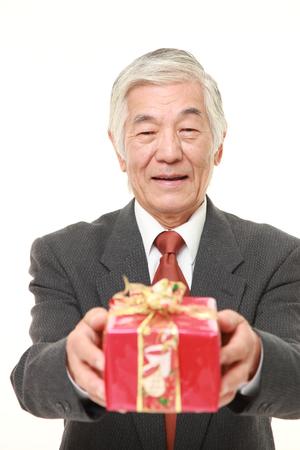 lazo regalo: senior Japanese businessman offering a gift