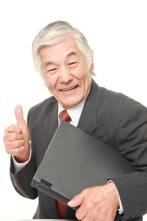 carrying: senior Japanese  businessman carrying laptop computer Stock Photo
