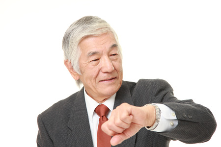 checking time: senior Japanese businessman checking time on his watch