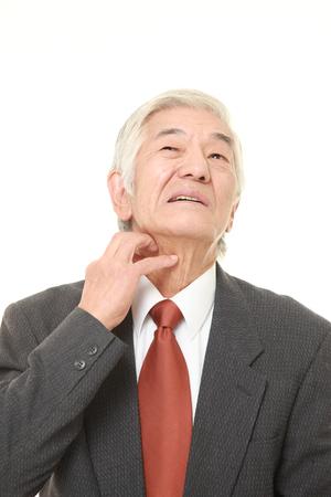 scratching: senior Japanese businessman scratching his neck