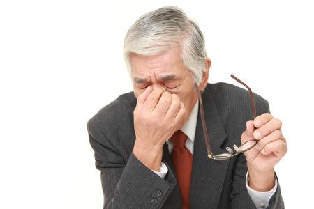シニア日本のビジネスマンに苦しんでいる眼精疲労 写真素材