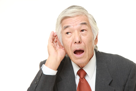 japanese people: senior Japanese businessman with hand behind ear listening closely