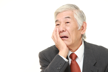 suffers: senior Japanese businessman suffers from toothache